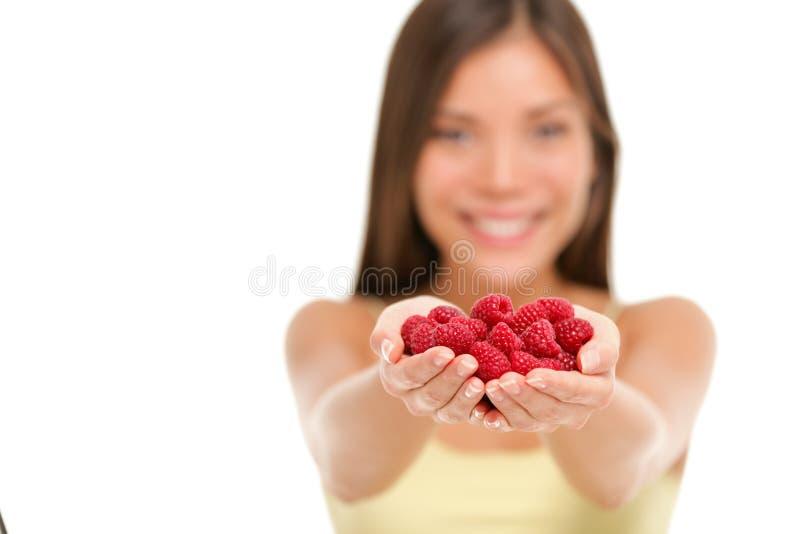 Mulher que guarda framboesas frescas no close up das mãos fotos de stock royalty free