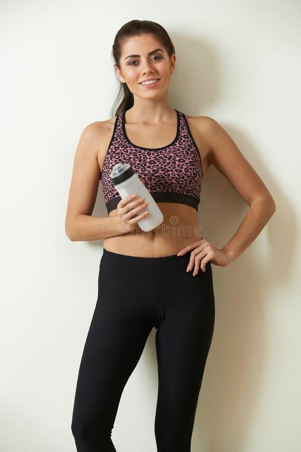 Mulher que guarda a garrafa de água que toma a ruptura durante o exercício foto de stock