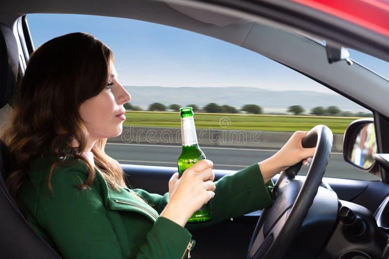 Mulher que guarda a garrafa de cerveja ao conduzir o carro fotografia de stock