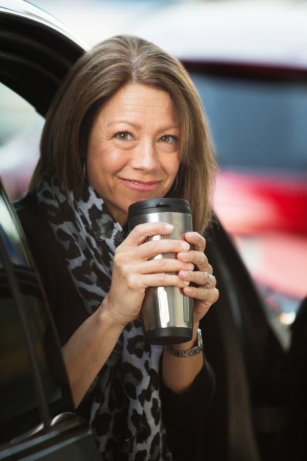 Mulher que guarda a garrafa térmica do café foto de stock royalty free