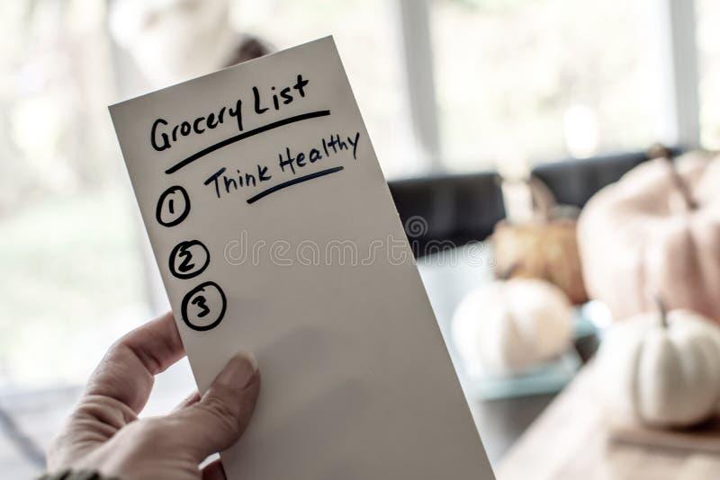 Mulher que guarda a lista de compras na mercearia para a definição saudável dos anos novos imagens de stock royalty free