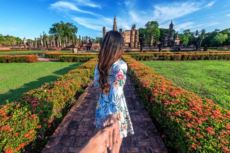 Mulher que guarda a mão do ` s do homem e que conduz o a Wat Mahathat Temple nos arredores do parque histórico de Sukhothai foto de stock royalty free