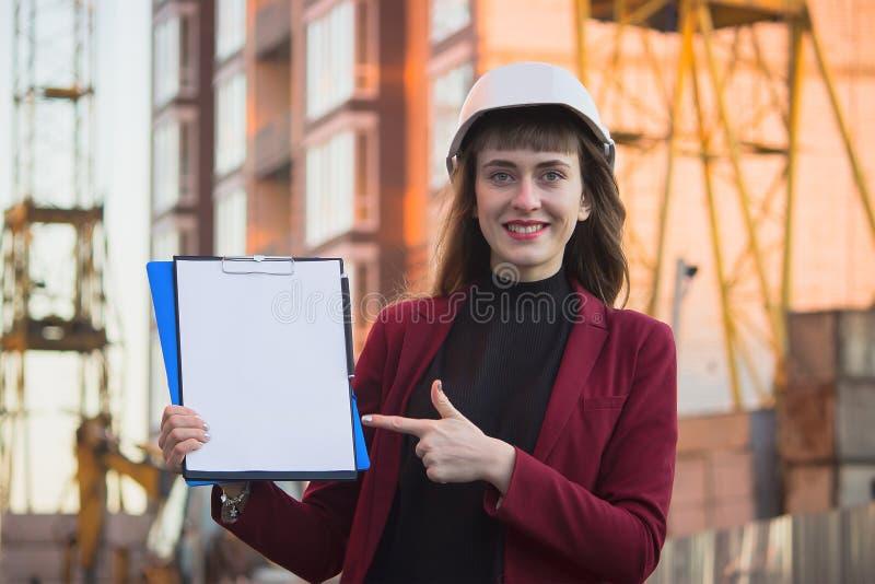 Mulher que guarda modelos, prancheta Arquiteto de sorriso no capacete na construção foto de stock