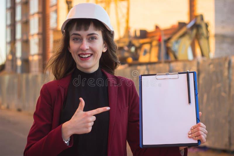 Mulher que guarda modelos, prancheta Arquiteto de sorriso no capacete na construção fotos de stock