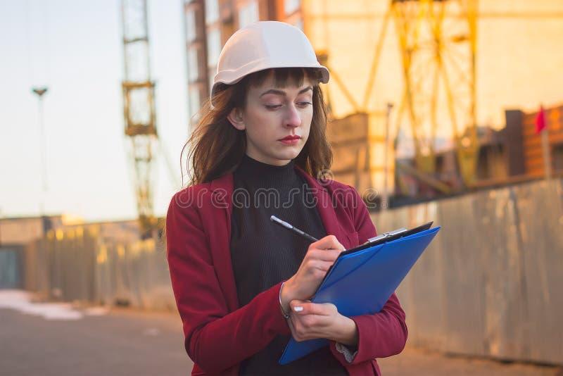Mulher que guarda modelos, prancheta Arquiteto de sorriso no capacete na construção imagem de stock