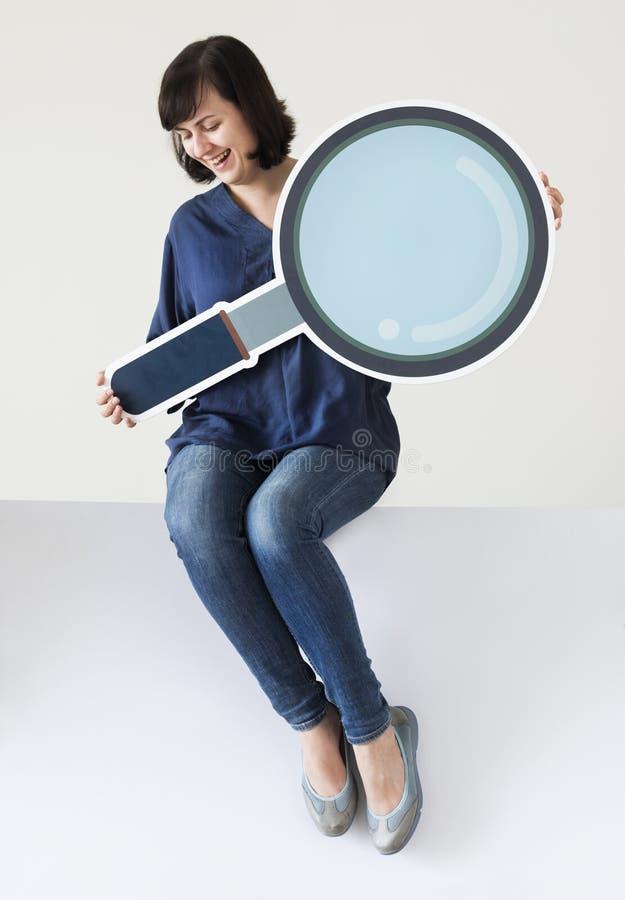Mulher que guarda o ícone da lupa fotografia de stock