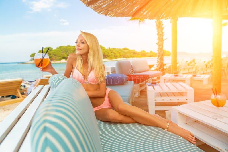 A mulher que guarda o aperol congelado clássico delicioso spritz o cocktail com cubos de gelo em uma praia tropical quente na luz imagens de stock