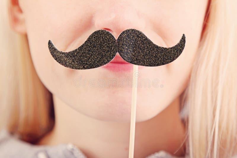 Mulher que guarda o bigode em uma vara foto de stock