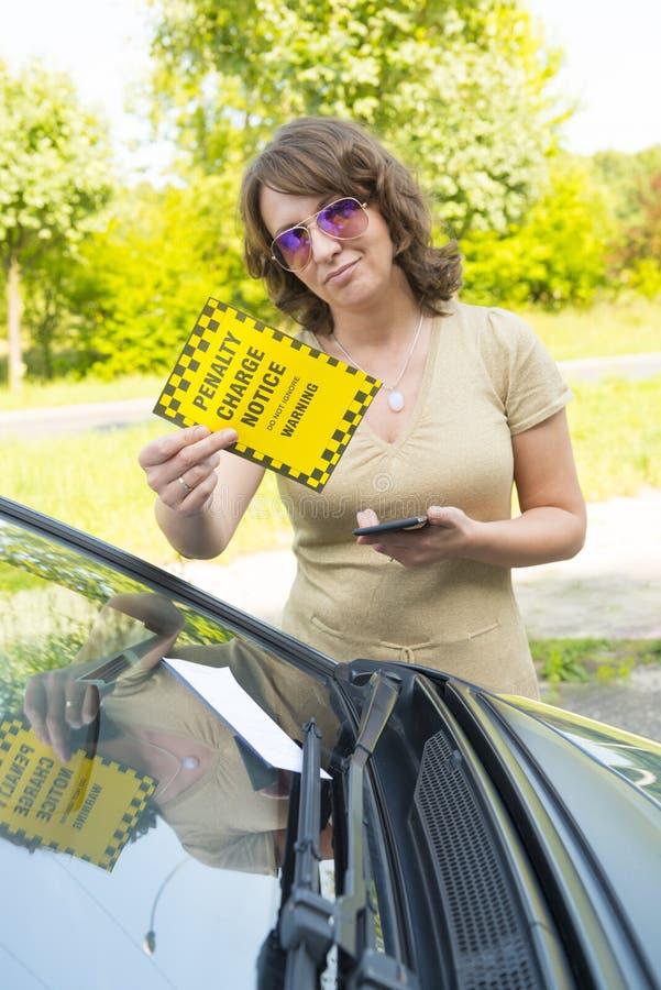 Mulher que guarda o bilhete de estacionamento fotografia de stock