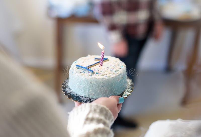 Mulher que guarda o bolo de aniversário com número 1 e vela imagem de stock