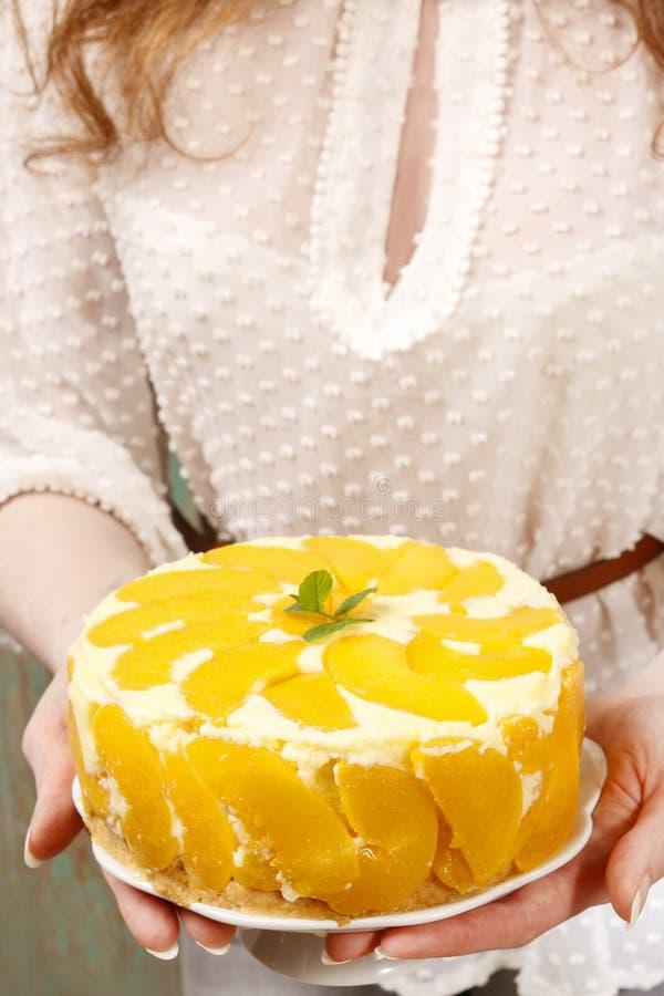 Mulher que guarda o bolo de queijo do pêssego foto de stock