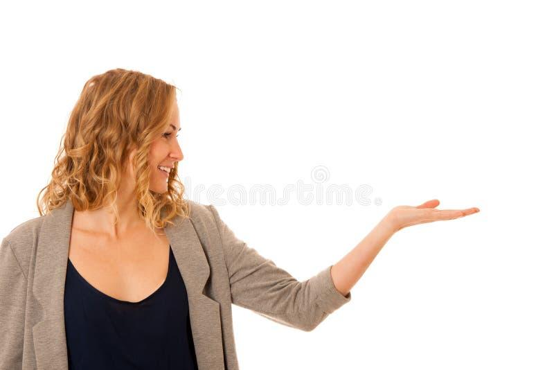 Mulher que guarda o braço sobre o espaço da cópia como está anunciando um produc foto de stock royalty free