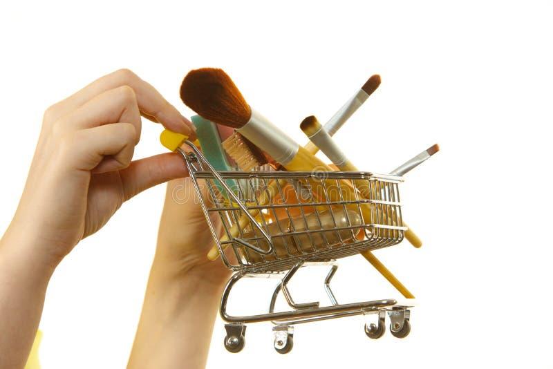 A mulher que guarda o carrinho de compras com comp?e escovas imagens de stock royalty free