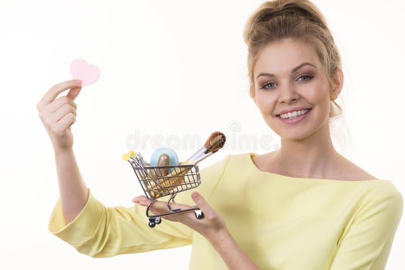 A mulher que guarda o carrinho de compras com comp?e escovas imagens de stock