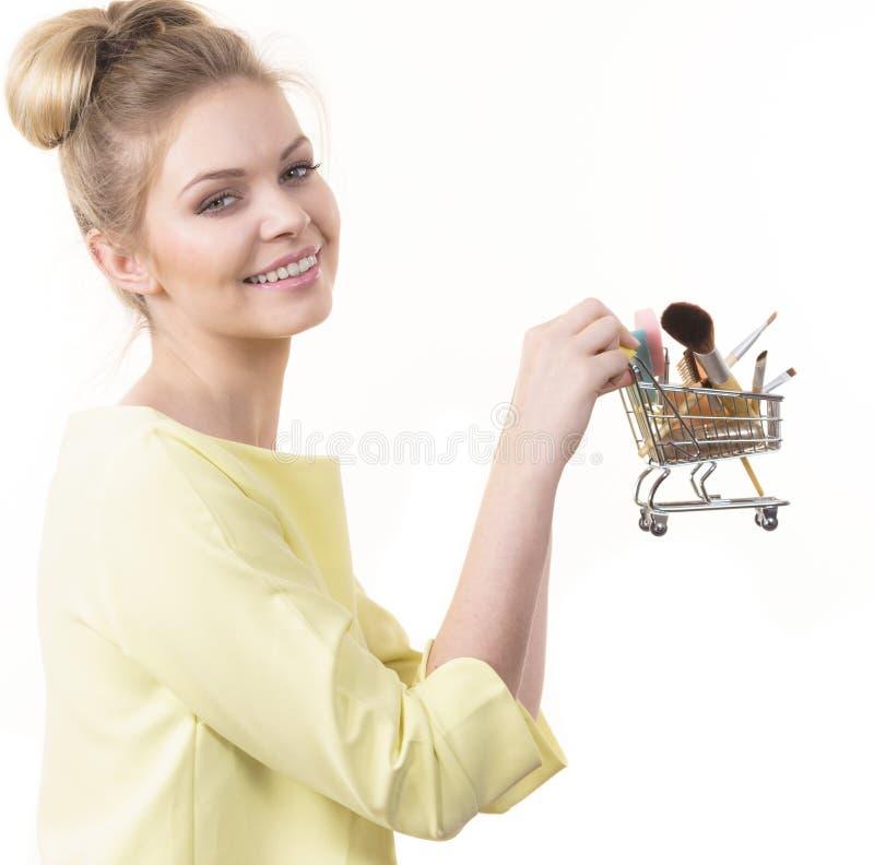A mulher que guarda o carrinho de compras com comp?e escovas fotografia de stock royalty free