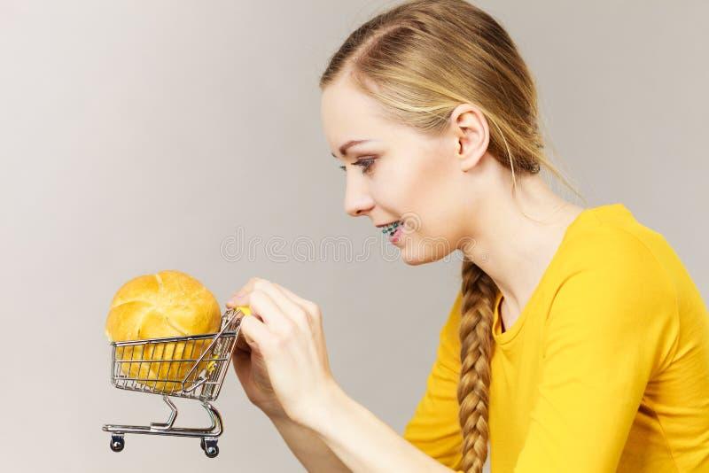 Mulher que guarda o carrinho de compras com p?o fotografia de stock royalty free