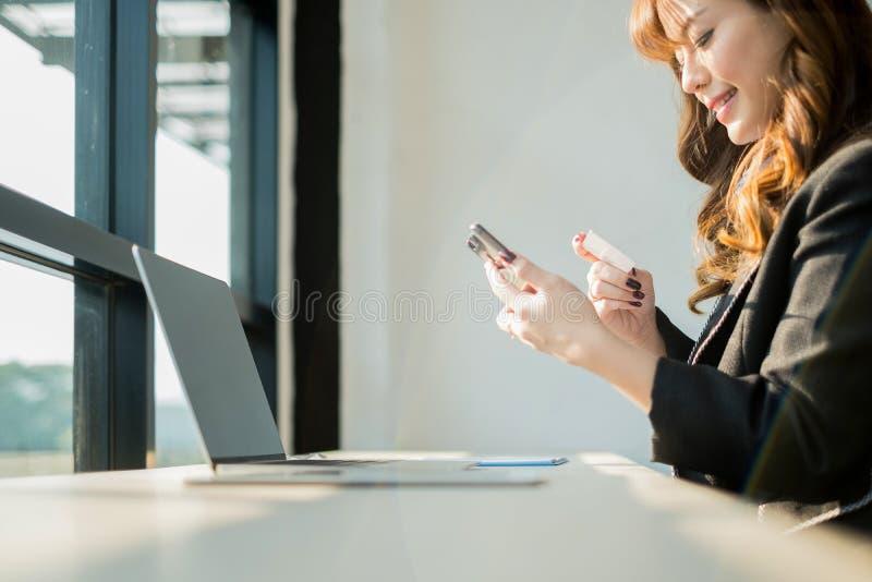 Mulher que guarda o cartão de crédito e que usa o Web site da compra do portátil e do smartphone em linha, conceito de compra imagens de stock