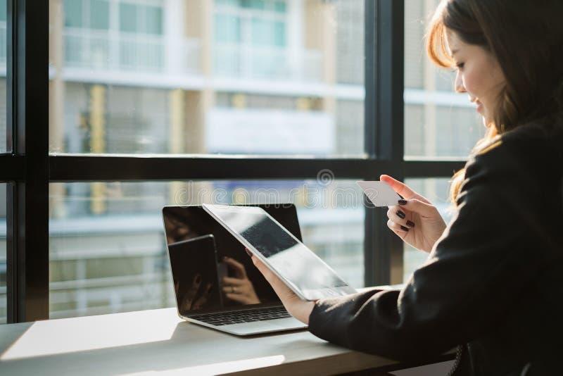 Mulher que guarda o cartão de crédito e que usa o Web site da compra do portátil e do smartphone em linha, conceito de compra foto de stock