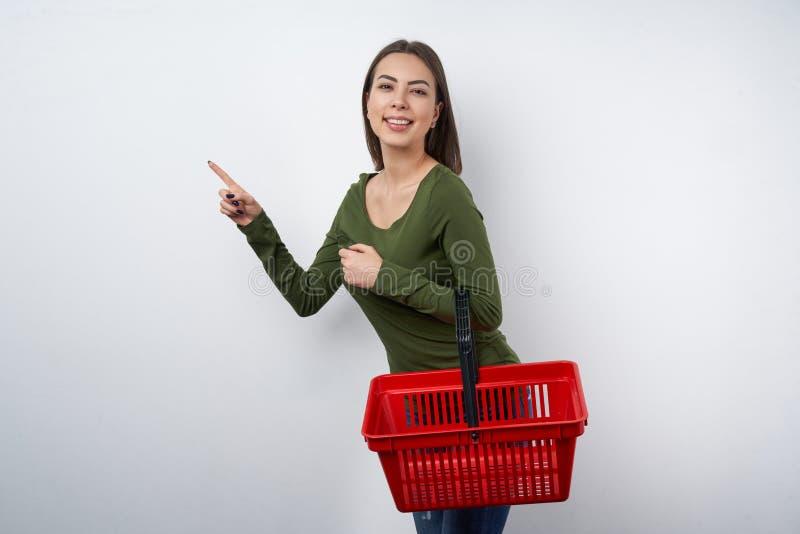 Mulher que guarda o cesto de compras vazio que aponta para tomar partido imagens de stock royalty free