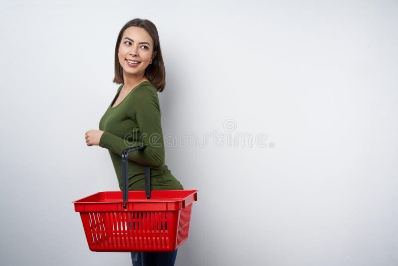 Mulher que guarda o cesto de compras vazio que olha de lado fotografia de stock