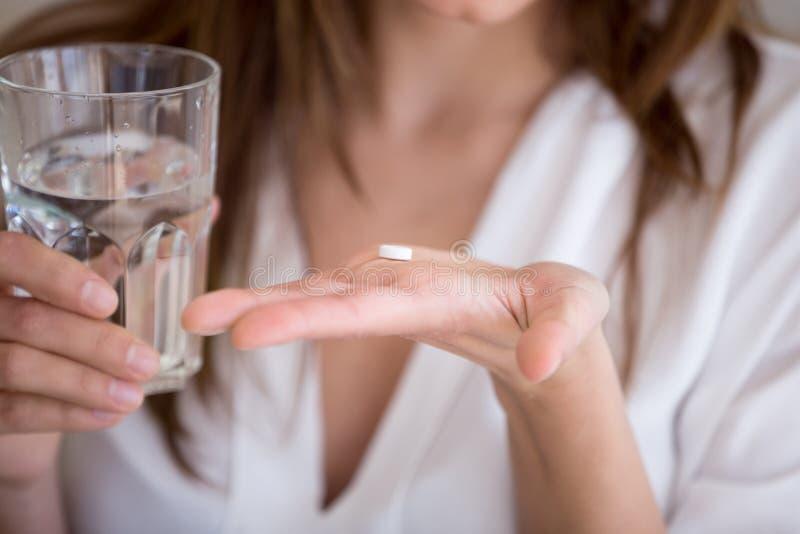 Mulher que guarda o comprimido e o vidro da água, fim acima da vista fotos de stock