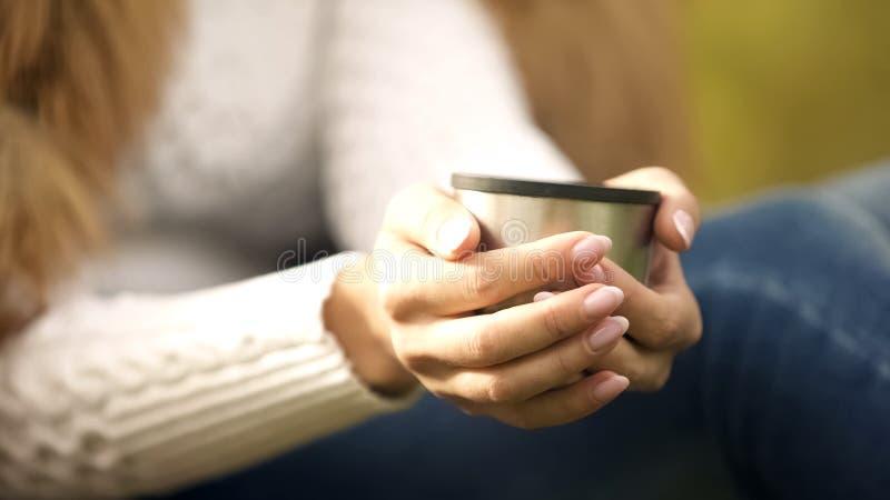 Mulher que guarda o copo da garrafa térmica com o close up da bebida do chá, tratamento de mãos delicado, cuidado do prego imagem de stock royalty free
