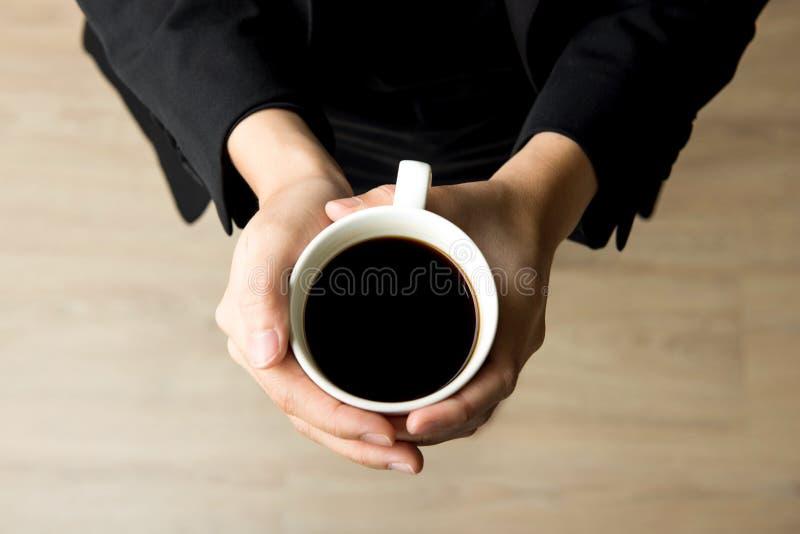 Mulher que guarda o copo de café com café preto - vista superior imagens de stock royalty free