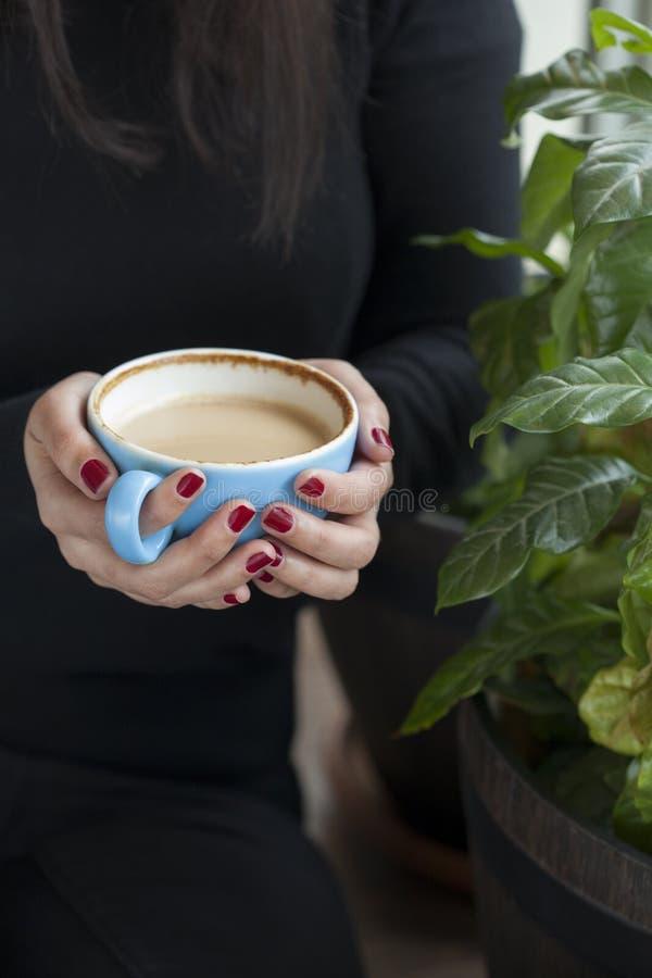 Mulher que guarda o copo de café com pregos vermelhos fotografia de stock royalty free