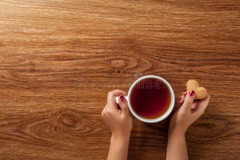 Mulher que guarda o copo quente do chá com cookies foto de stock