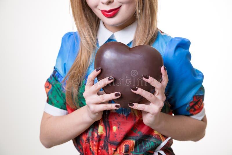Mulher que guarda o coração grande do chocolate doce fotografia de stock royalty free