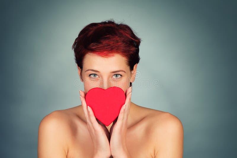 Mulher que guarda o coração vermelho na frente de sua cara fotos de stock royalty free