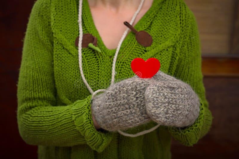 Mulher que guarda o coração vermelho nas mãos imagem de stock