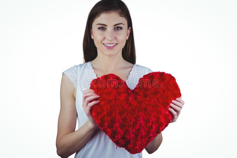 Mulher que guarda o coxim da forma do coração imagens de stock