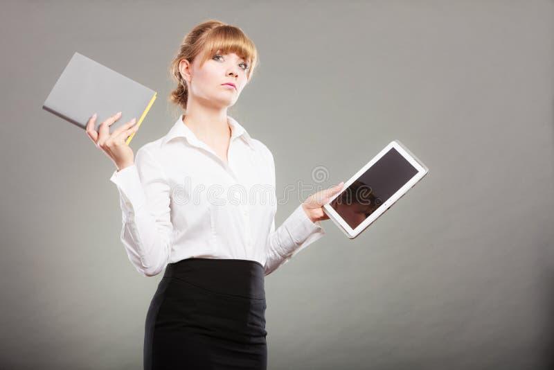 Mulher que guarda o ebook e o livro Instrução moderna imagens de stock