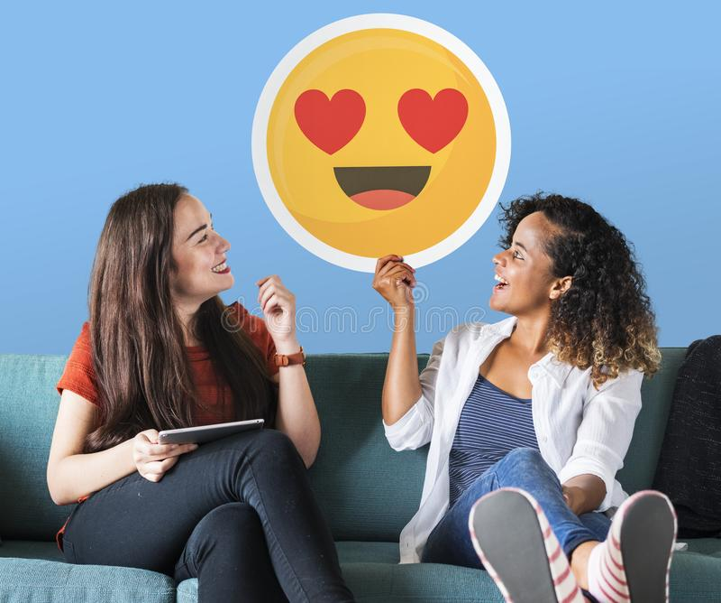 Mulher que guarda o emoticon expressivo em um sofá imagem de stock