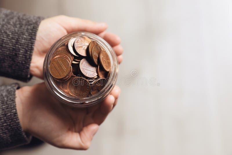 Mulher que guarda o frasco da doação com as moedas no fundo claro, vista superior foto de stock royalty free