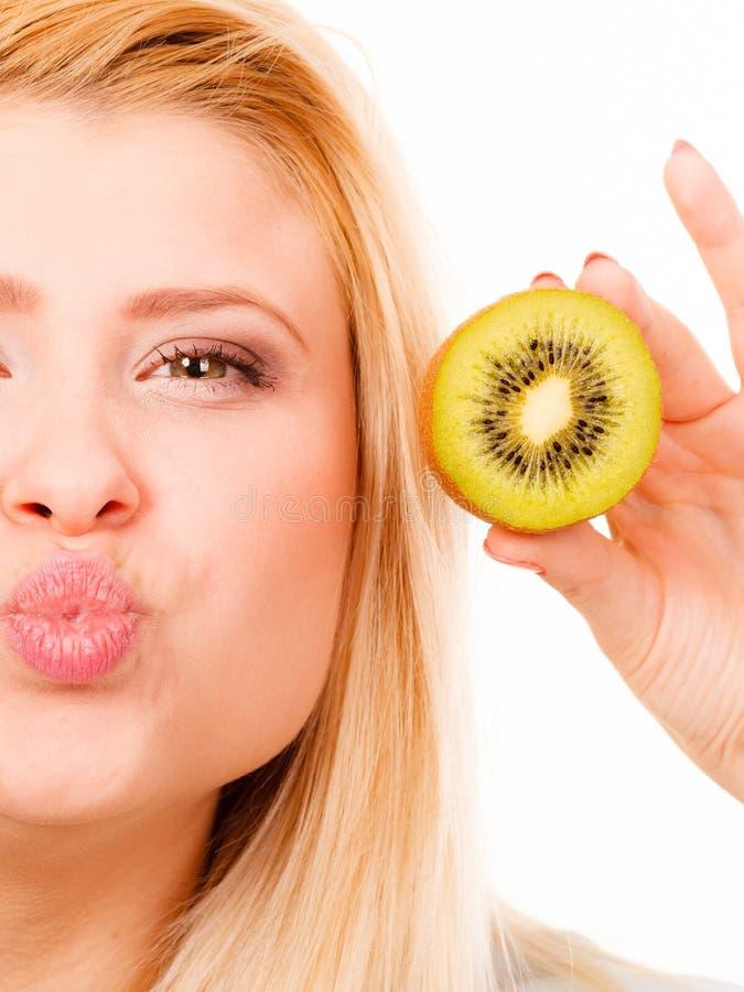 Mulher que guarda o fruto de quivi verde fotos de stock