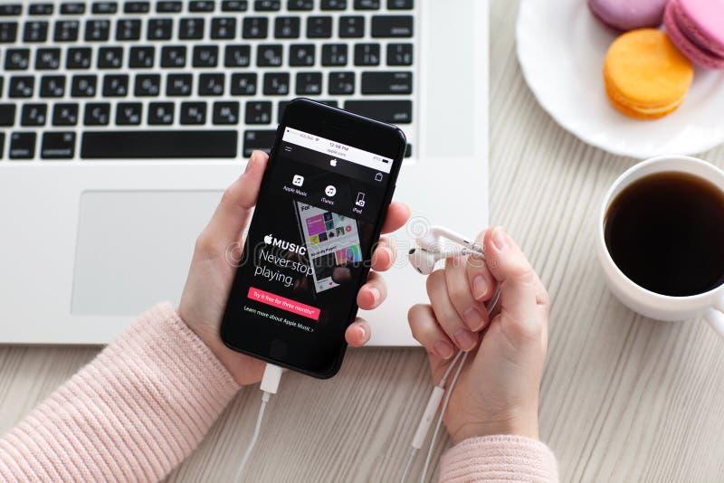 Mulher que guarda o iPhone 7 Jet Black Onyx com música de Apple foto de stock