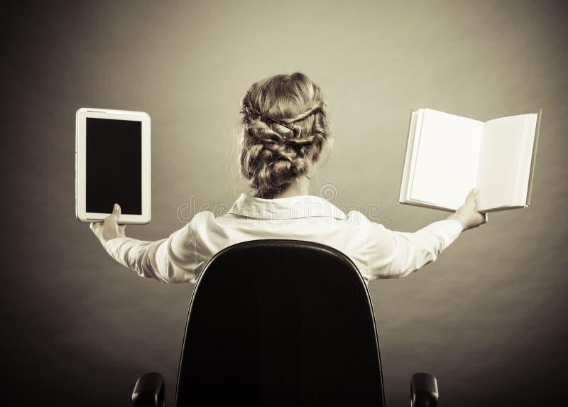 Mulher que guarda o livro e o leitor tradicionais do eBook imagem de stock