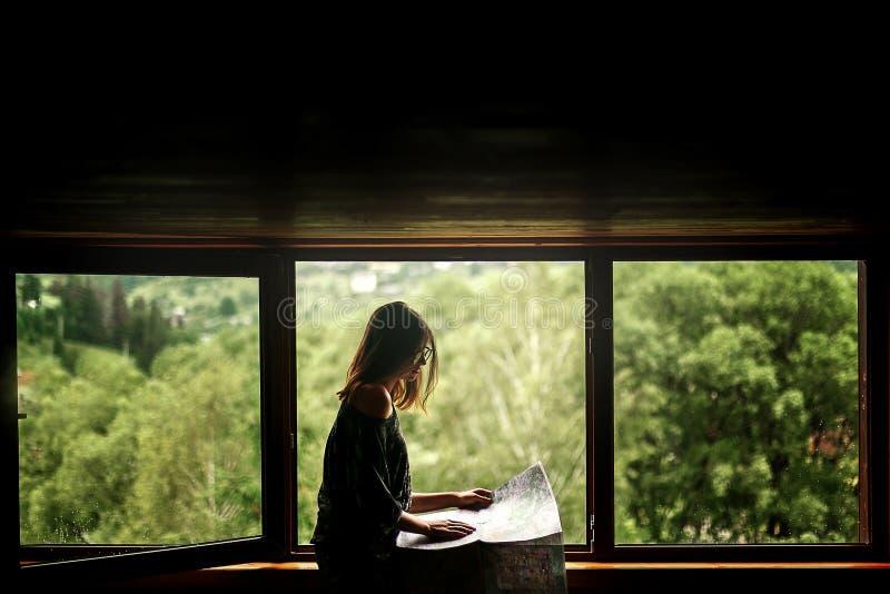 Mulher que guarda o mapa que senta-se na janela com vista em mountai surpreendente fotografia de stock royalty free