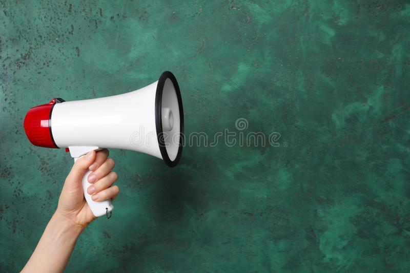 Mulher que guarda o megafone no fundo da cor foto de stock