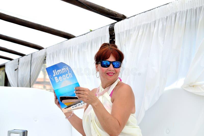 mulher que guarda o menu no restaurante Jimmy Beach em Torremolinos, Costa del Sol da praia do chiringuito, Espanha fotos de stock royalty free