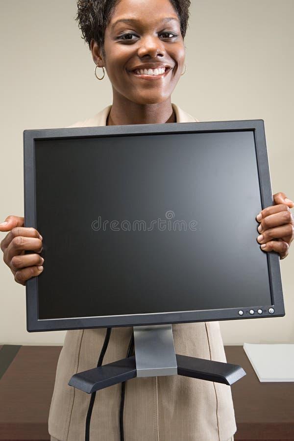 Mulher que guarda o monitor do computador fotos de stock