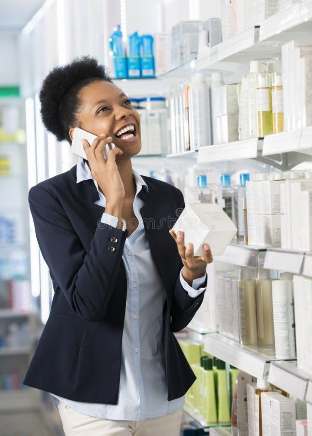 Mulher que guarda o produto ao comunicar-se no telefone celular imagens de stock