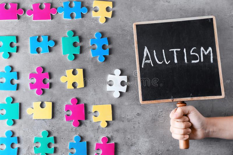 Mulher que guarda o quadro com ` do autismo do ` da palavra perto das partes coloridas de enigma foto de stock royalty free