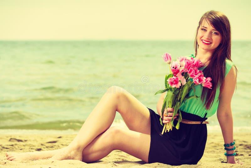 Mulher que guarda o ramalhete das flores que sentam-se na praia foto de stock royalty free