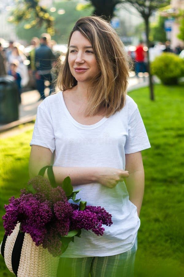 Mulher que guarda o saco da palha com grupo v?vido de flores lil?s foto de stock