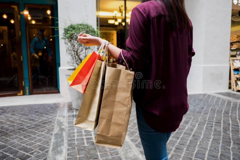 Mulher que guarda o saco de compras ao andar na rua do vintage, loja fotografia de stock