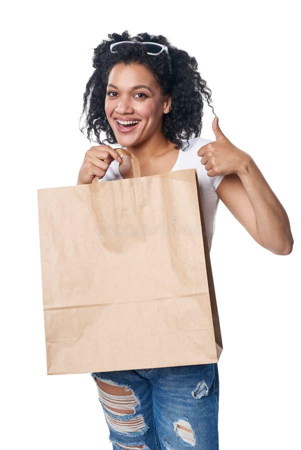 Mulher que guarda o saco de compras do ofício com espaço vazio da cópia e que gesticula o polegar acima fotografia de stock