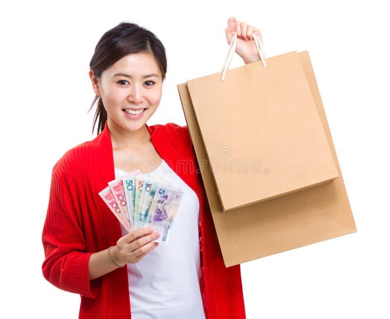 Mulher que guarda o saco de compras e o dinheiro fotos de stock